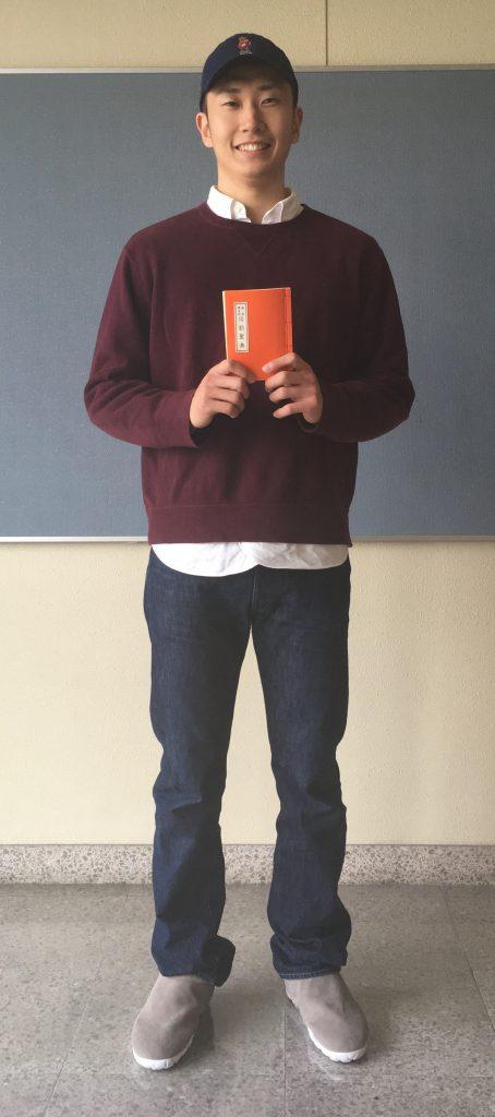 お経「同朋聖典」を手に笑顔の菊池広明選手