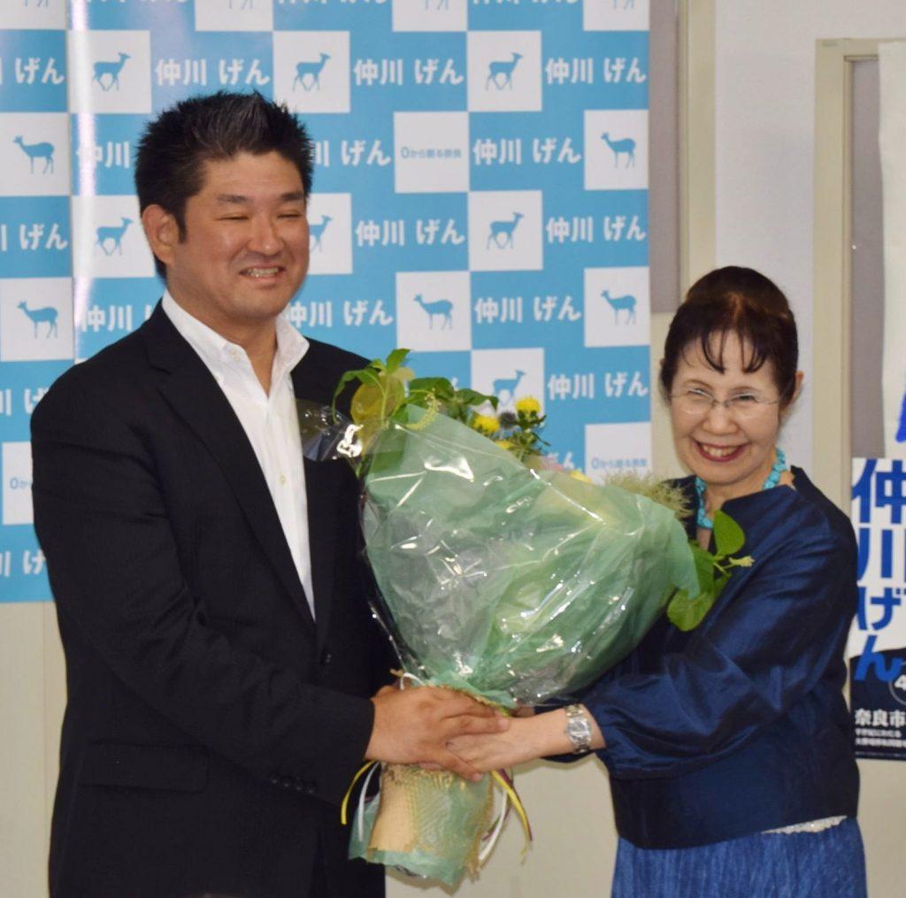 激戦を制し、支持者から花束を受け取る仲川氏(左)