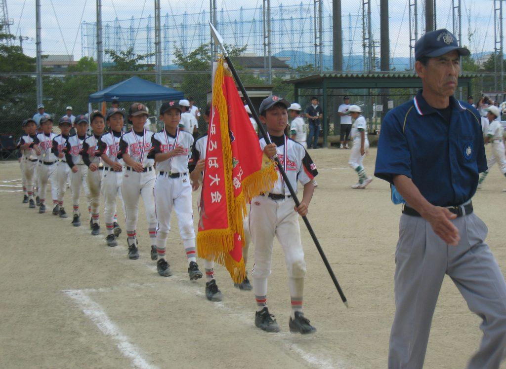 優勝し、胸を張ってグラウンドを行進する高田イーグルスの選手
