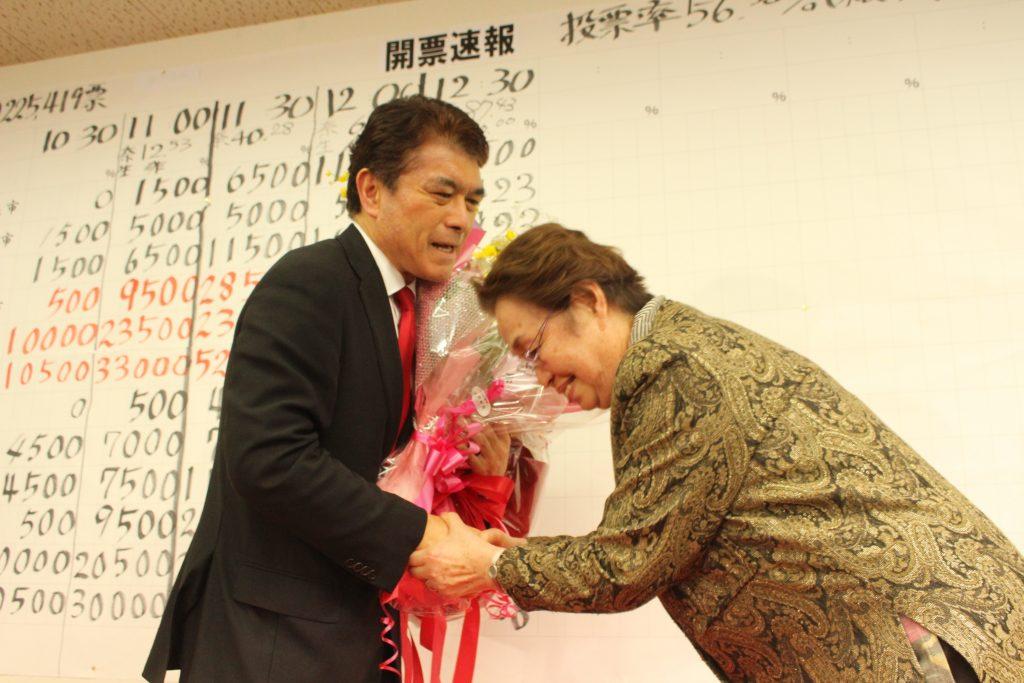 悲願の選挙区初当選を果たし、感極まった表情で花束を受け取る小林茂樹氏