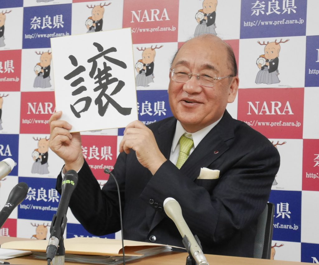 自筆の「譲」の漢字を掲げる荒井正吾知事
