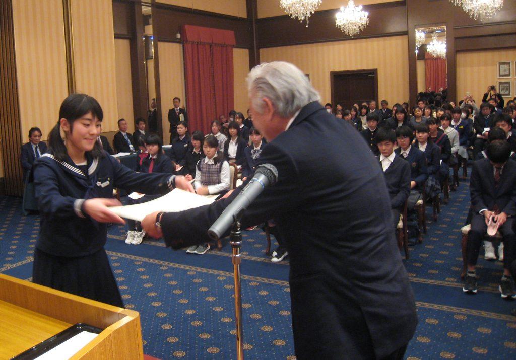 県納税貯蓄組合総連合会の尾川欣司会長から表彰状を受け取る今村美月さん(左)